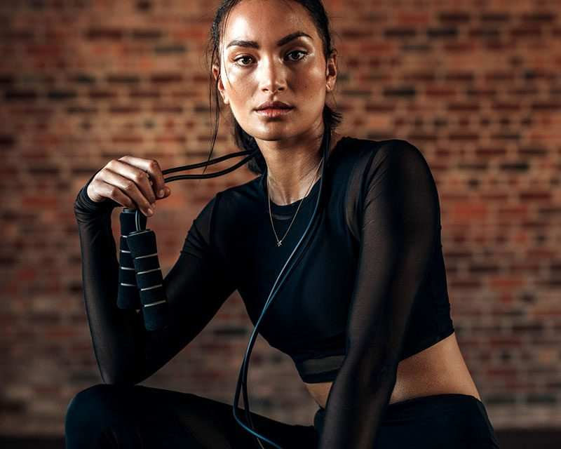 woman with black shirt holding jump rope around her neck