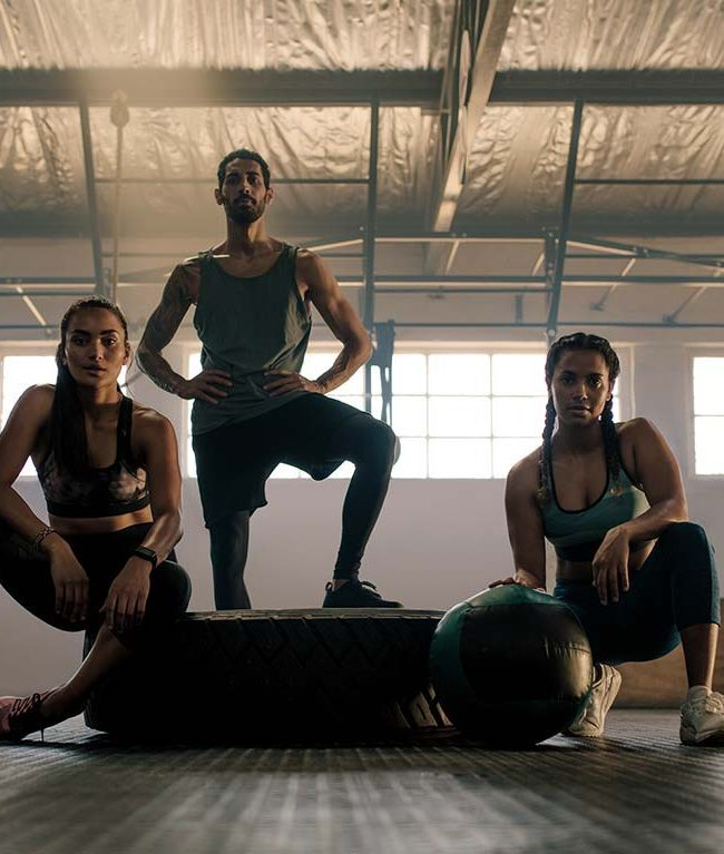 3 people looking at camera in a gym