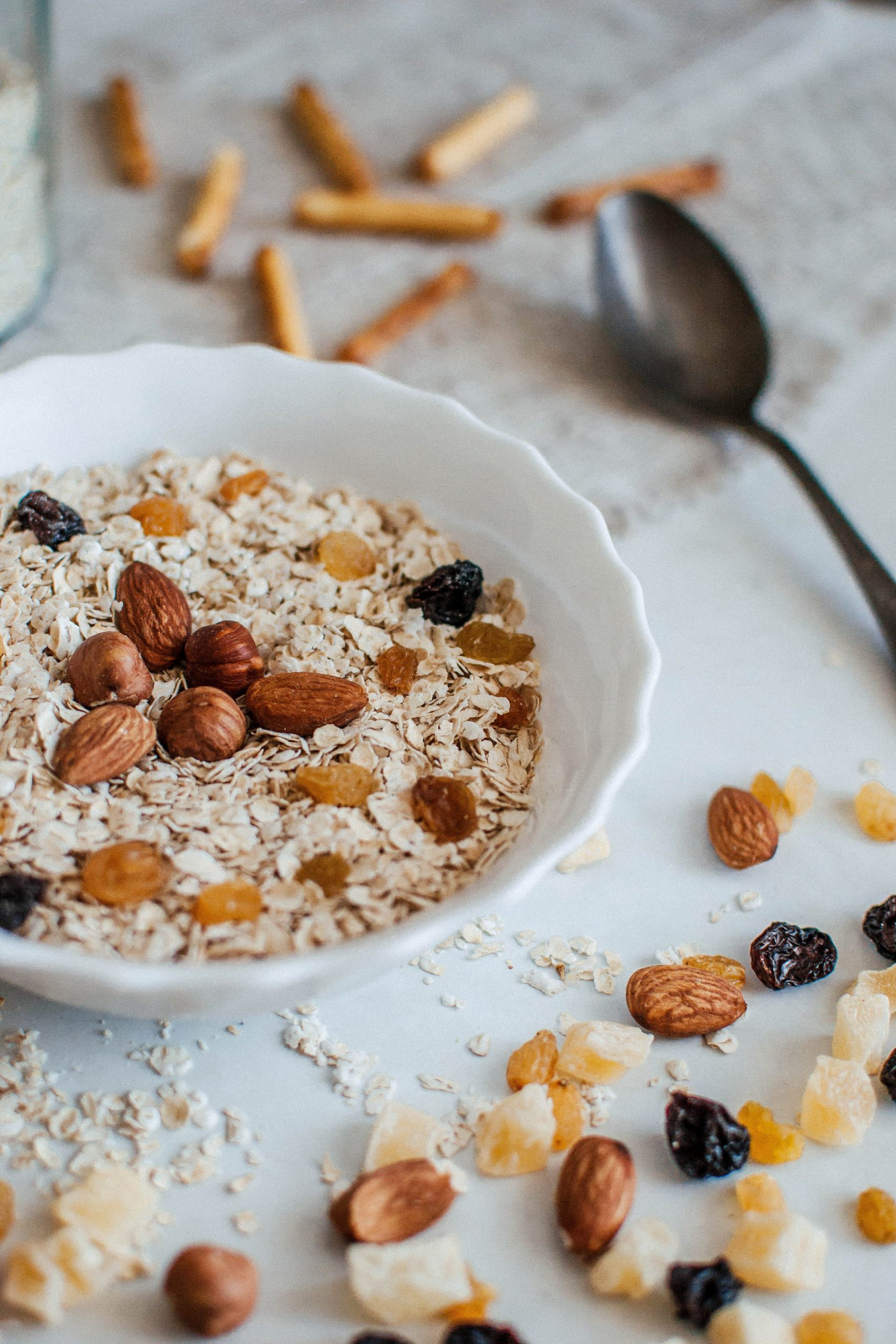 Oatmeal in a bowl with nuts and raisins scattered around, good nutrition