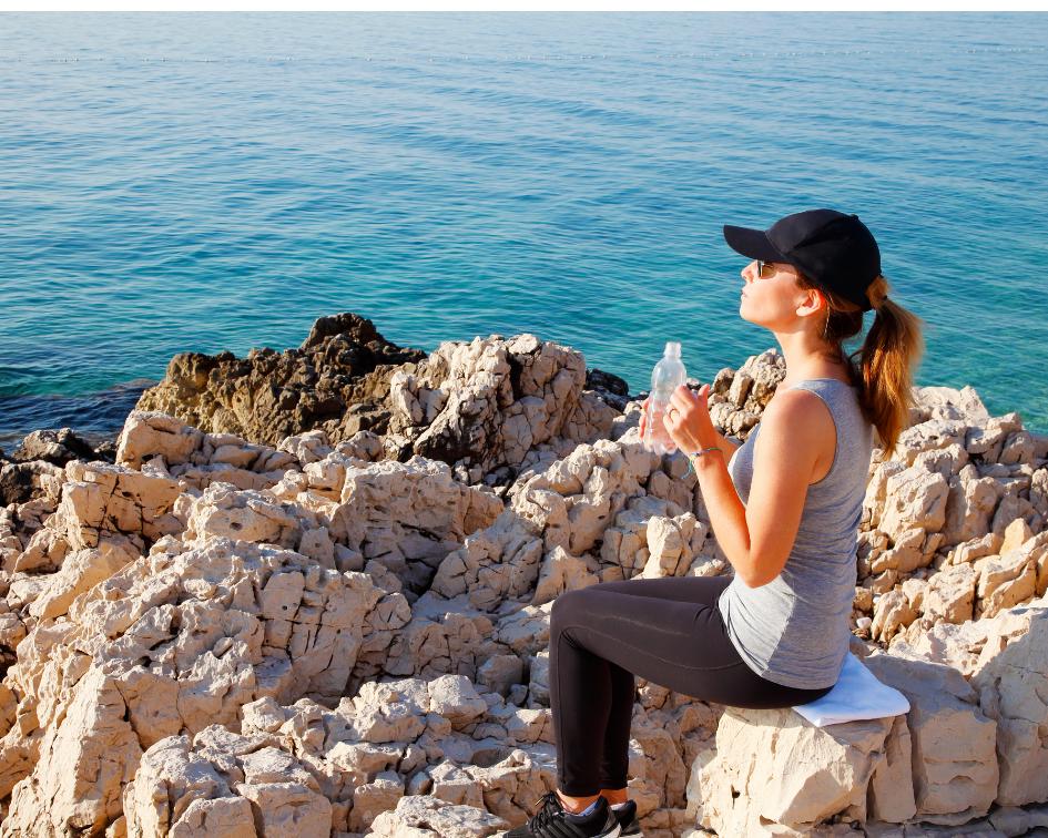 Girls sitting on rocks drinking a bottle of water